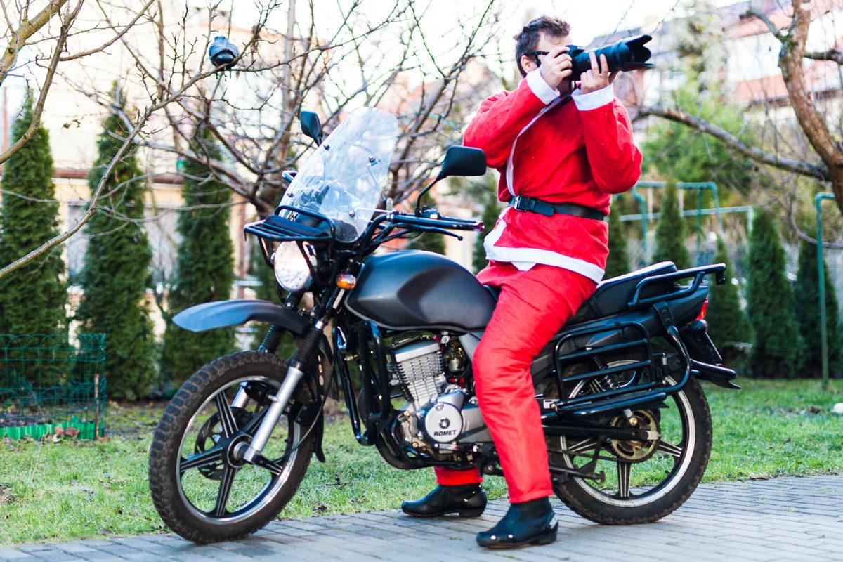 Motocyklowy Św. Mikołaj z aparatem w dłoni